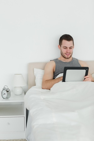 Portrait of an attractive man using a tablet computer in his bedroom photo