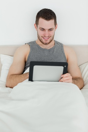 Portrait of a smiling man using a tablet computer in his bedroom photo