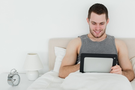 Peaceful man using a tablet computer in his bedroom photo