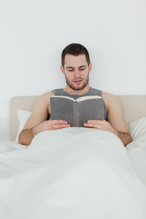 Portrait of a man reading a novel in his bedroom photo