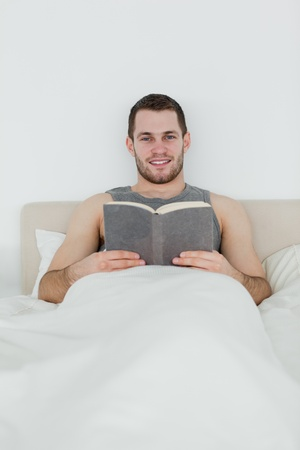 Portrait of a man reading a book in his bedroom photo