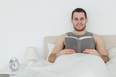 Man reading a book in his bedroom Stock Photo - 11636327