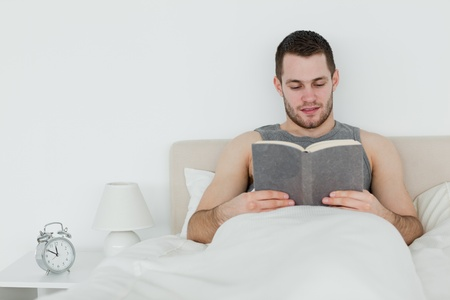 Man reading a novel in his bedroom photo
