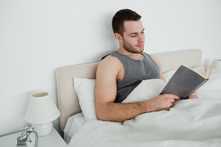 Young man reading a novel in his bedroom Stock Photo - 11633318