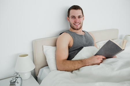 Smiling man reading a novel in his bedroom photo