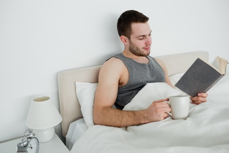 Smiling man reading a novel while having a tea in his bedroom Stock Photo - 11633281