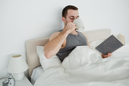 Smiling man reading a novel while drinking a coffee in his bedroom Stock Photo - 11634314