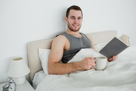 Young man reading a novel while drinking a coffee in his bedroom Stock Photo - 11634359