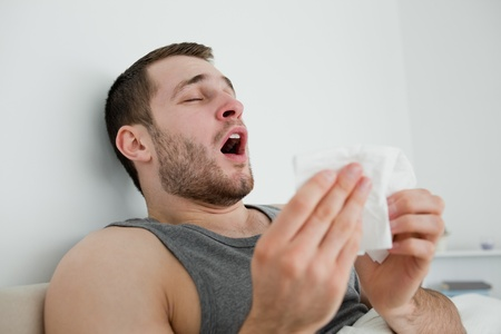 Sick man sneezing in his bedroom photo