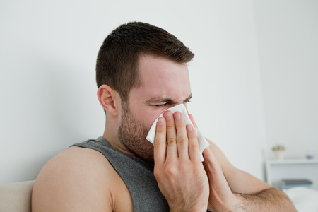 Sick man blowing his nose in his bedroom photo