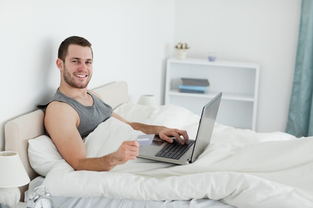 Smiling man purchasing online in his bedroom photo