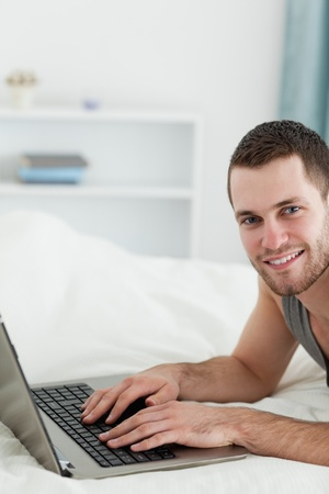 Portrait of a man using a laptop while lying on his belly in his bedroom photo