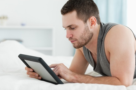 Handsome man using a tablet computer while lying on his belly in his bedroom photo