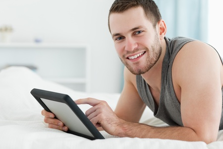 Smiling man using a tablet computer while lying on his belly in his bedroom photo