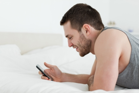 Man using his mobile phone in his bedroom photo