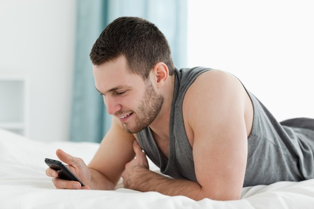 Young man using his mobile phone in his bedroom photo