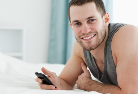 Smiling man using his mobile phone in his bedroom photo