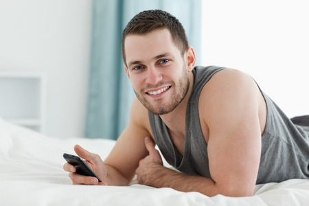 Happy man using his mobile phone in his bedroom photo