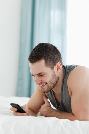Portrait of a young man using his mobile phone in his bedroom photo