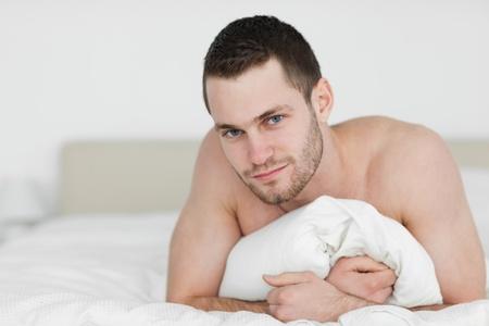 hombre desnudo: Hombre guapo acostado sobre el vientre en su dormitorio