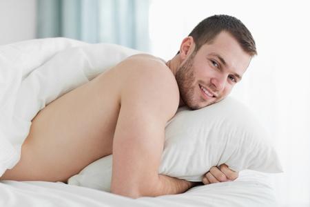 naked man: Joven calma acostado sobre el vientre en su dormitorio