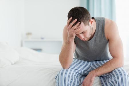 pyjamas: Hombre triste sentado en su cama con su cabeza en la mano
