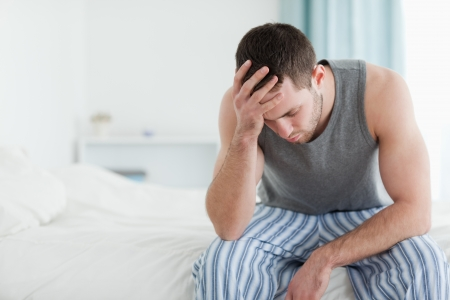 sick in bed: Sad man sitting on his bed with his head on his hand Stock Photo