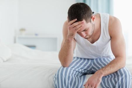 persona sentada: Hombre enfermo sentado en su cama con su cabeza en la mano