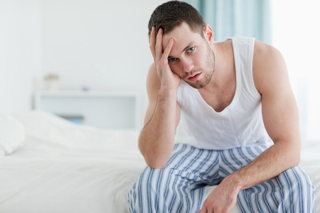 Depressed man sitting on his bed while looking at the camera Stock Photo - 11634380