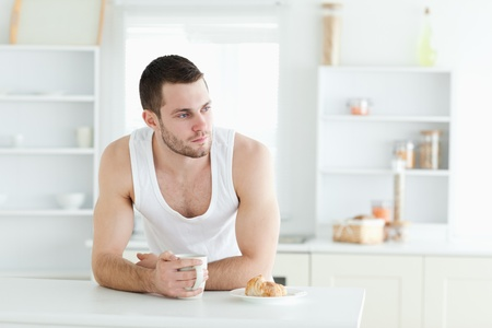 Bel homme prenant le petit déjeuner dans sa cuisine