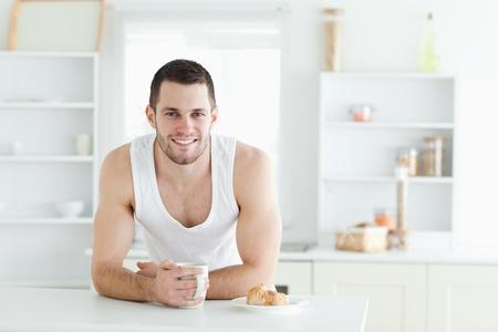 Happy man having breakfast in his kitchen photo