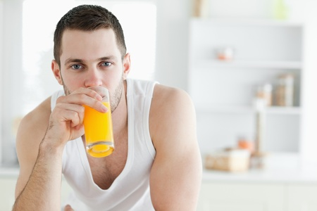 good looking man: Good looking man drinking orange juice in his kitchen
