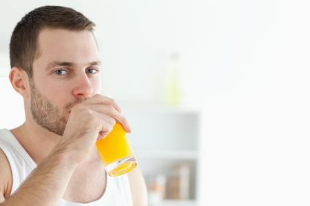good looking man: Portrait of a good looking man drinking orange juice in his kitchen