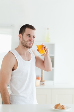 Portrait of a smiling man drinking orange juice in his kitchen photo