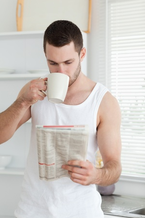 Portrait of a man drinking tea while reading the news in his kitchen photo