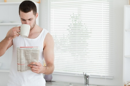 Man drinking tea while reading the news in his kitchen photo
