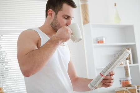 Young man drinking coffee while reading the news in his kitchen photo