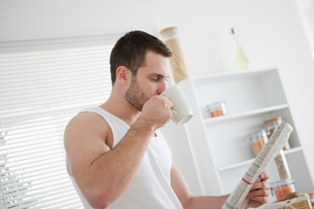 Young man drinking tea while reading the news in his kitchen photo
