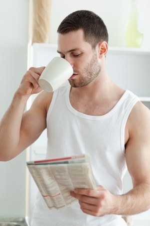 Portrait of a young man drinking tea while reading the news in his kitchen photo