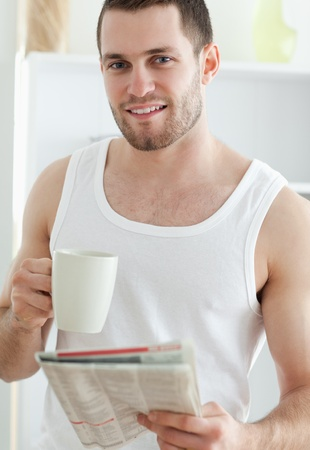 Portrait of a handsome man drinking coffee while reading the news in his kitchen photo