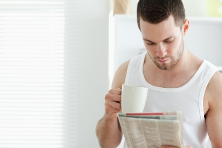 Smiling man drinking coffee while reading the news in his kitchen photo