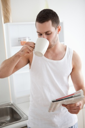 Portrait of a smiling man drinking tea while reading the news in his kitchen photo
