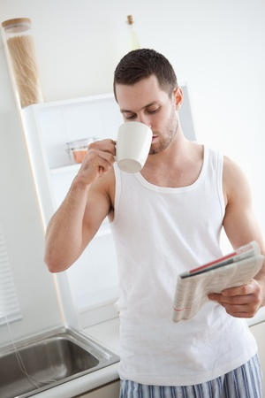 Portrait of a good looking man drinking tea while reading the news in his kitchen photo