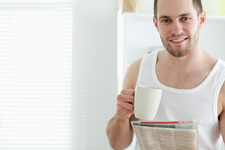 Good looking man drinking tea while reading the news in his kitchen photo