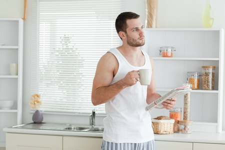 Good looking man drinking coffee while reading the news in his kitchen photo