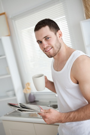 Delighted man drinking coffee while reading the news in his kitchen photo