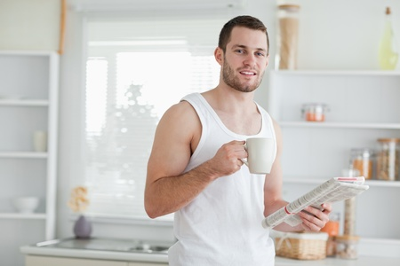 Delighted man drinking tea while reading the news in his kitchen photo