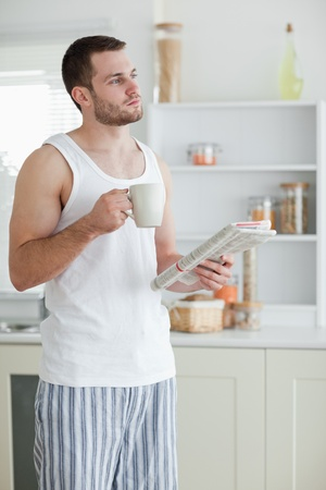 Portrait of a sports man drinking tea while reading the news in his kitchen photo