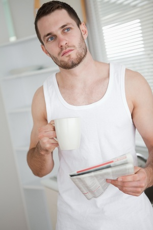 Portrait of a healthy man drinking tea while reading the news in his kitchen photo