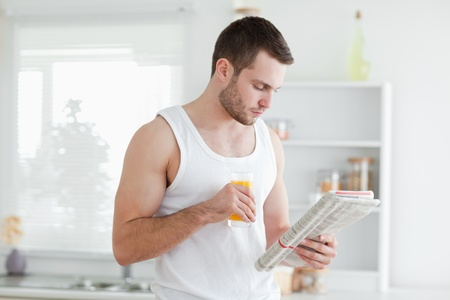 Man drinking orange juice while reading the news in his kitchen photo